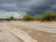 The desert sands washed completely across the road. More wild weather to come? Looks like it!
